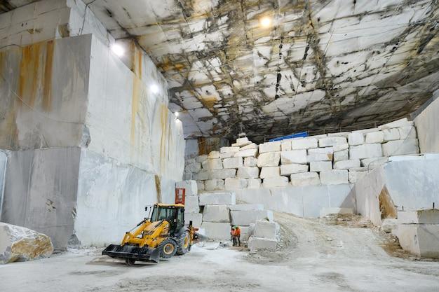 Arbeiter und maschinen in einem marmorsteinbruch oder einer tagebaugrube während der ausgrabung des weißen steins in einem berg in carrara, toskana, italien