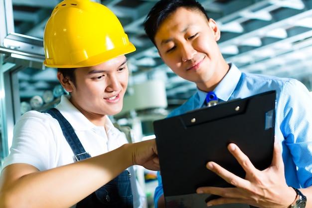 Arbeiter und produktionsleiter mit zwischenablage