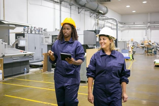 Arbeiter zeigt und spricht mit kollegen und hält tablette