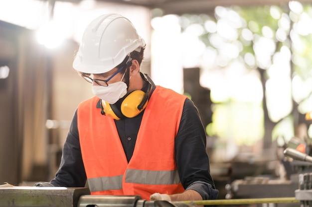 Arbeiterfabrikmann, der gesichtsmaske trägt und an schwerer maschine arbeitet.