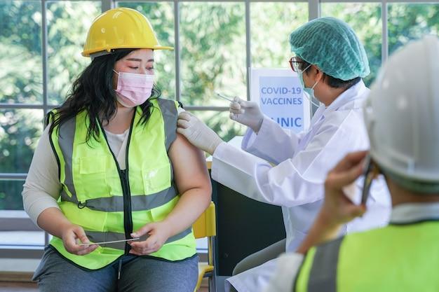 Arbeiterfrau, die sitzt, um einen covid-impfstoff mit einer krankenschwester zu erhalten, die den impfstoff injiziert, um immunität zu erhalten