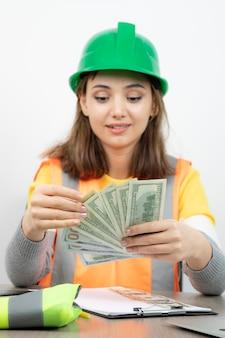 Arbeiterfrau in orangefarbener weste und grünem helm, die am schreibtisch sitzt.