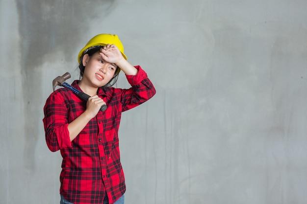 Arbeiterfrau müde und hammer auf der baustelle haltend