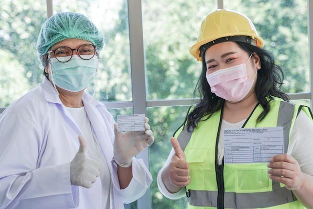 Arbeiterfrau und krankenschwester, die nach der injektion des impfstoffs einen covid-19-impfpass vorzeigen