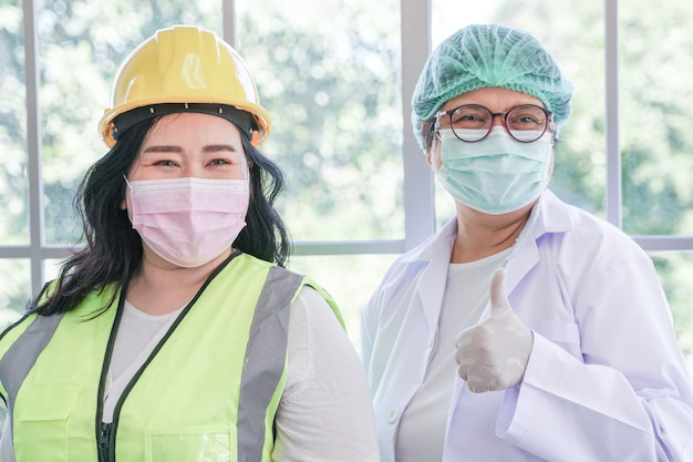 Arbeiterfrau und krankenschwester stehen mit vertrauen in die karriere berufstätige in der industrie