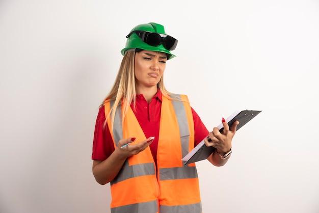 Arbeiterfrauenindustrie in der weste, die auf zwischenablage schaut