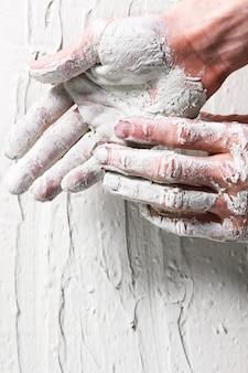 Arbeiterhände im weißen stuckhintergrund, flach. reparatur, bauarbeiten, bau, verputzkonzept