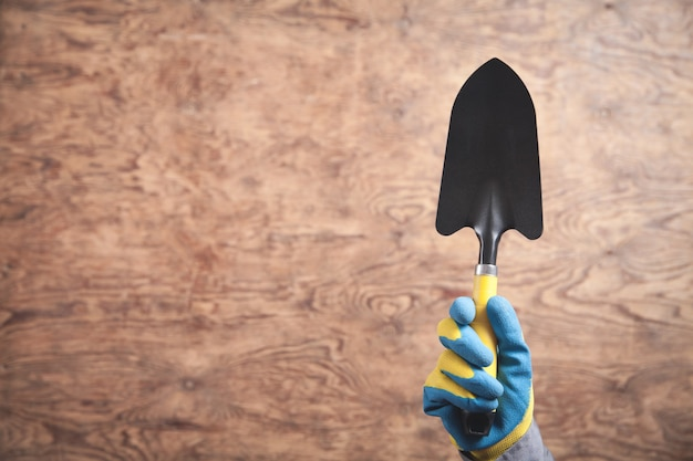 Arbeiterhand, die kleine schaufel zeigt