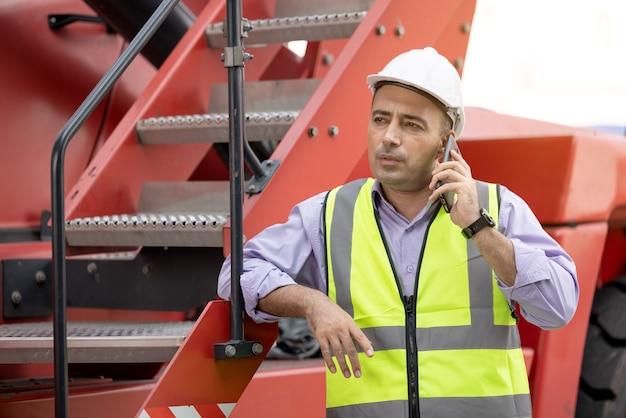 Arbeiterhelm, der auf mobiltelefon am versandhof der logistischen frachtcontainer steht und spricht