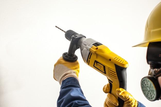 Arbeiterin bohrt die wand, harte arbeit für frauen