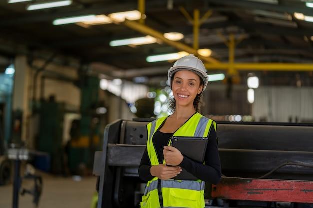 Arbeiterin der fabrik, die mit zwischenablage in den händen arbeitet und prüft, die notwendige notizen im werk machen.