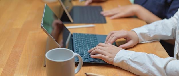 Arbeiterin, die auf digitalem tablett tippt, während sie mit ihrem kollegen am gemeinsamen arbeitsraum sitzt