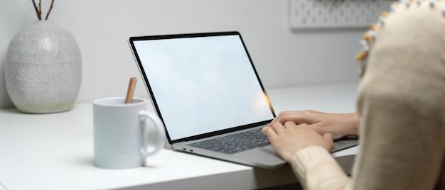 Arbeiterin, die auf laptop mit kaffeetasse und keramikvase auf weißem arbeitstisch tippt