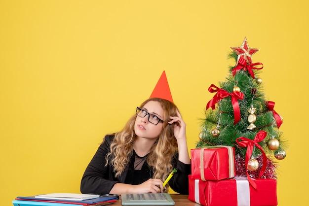 Arbeiterin, die hinter ihrem arbeitsplatz sitzt und an gelb denkt