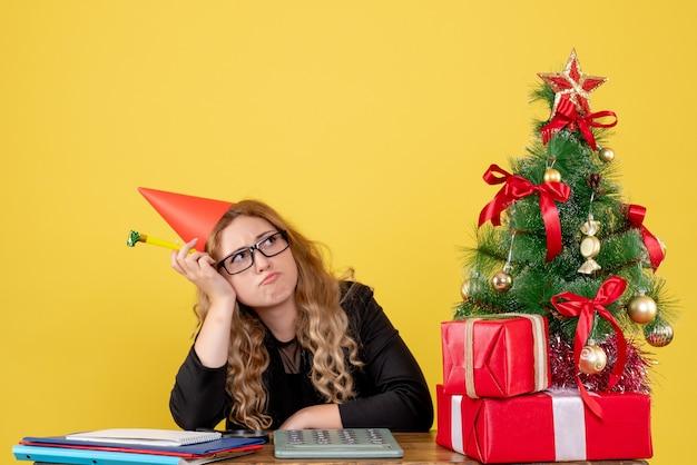 Arbeiterin, die hinter ihrem arbeitsplatz sitzt und sich auf gelb langweilt