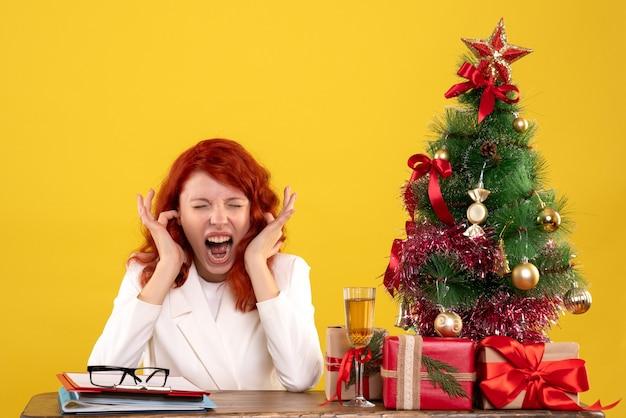 Arbeiterin, die hinter tisch mit weihnachtsgeschenken und baum auf gelb sitzt