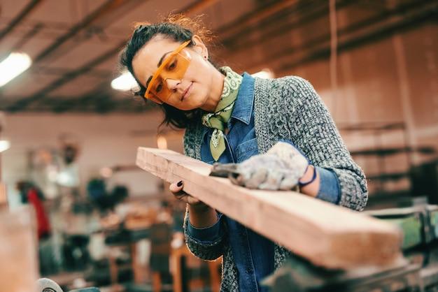 Arbeiterin, die hölzernen balken verarbeitet, der schutzhandschuhe und -brille trägt.