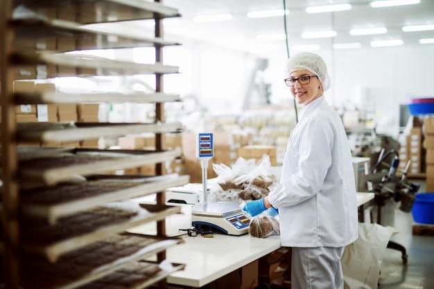 Arbeiterin, die kekse misst und sie in plastiktüten steckt, während sie steht und kamera betrachtet. innenausstattung der lebensmittelfabrik.