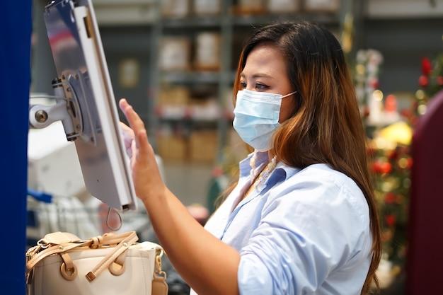 Arbeiterin, die lagerbestand der produkte während der arbeit im großen lager inspiziert.