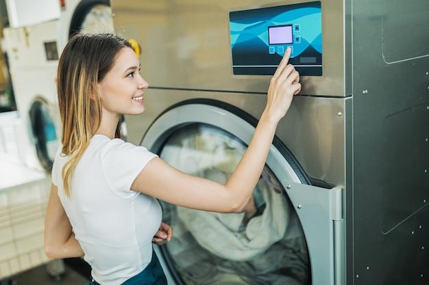 Arbeiterin, die mit der wäsche arbeitet, arbeitet mit einer industriewaschmaschine.
