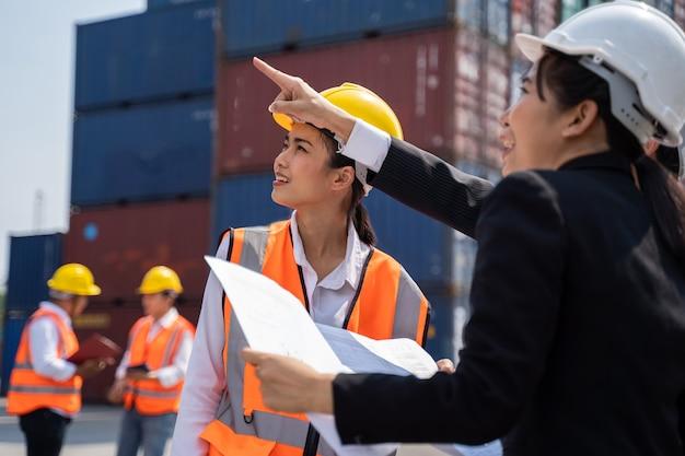 Arbeiterin, die mit foreman arbeitet und mit einem gelben helm steht, um das laden zu kontrollieren und die qualität von containern vom frachtschiff für den import und export in der werft oder im hafen zu überprüfen