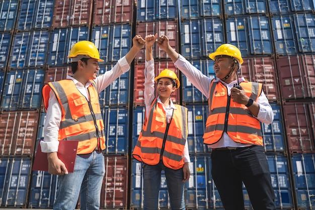 Arbeiterin, die mit ihrem kollegen arbeitet und mit einem gelben helm steht, um das laden zu kontrollieren und die qualität von containern vom frachtschiff für den import und export in der werft oder im hafen zu überprüfen