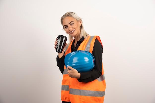 Arbeiterin, die mit tasse kaffee auf weißem hintergrund aufwirft. hochwertiges foto