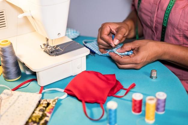 Arbeiterin, die nähmaschine beim herstellen von medizinischen gesichtsmasken während des ausbruchs des coronavirus verwendet - hausgemachtes herstellungskonzept der rechten hand