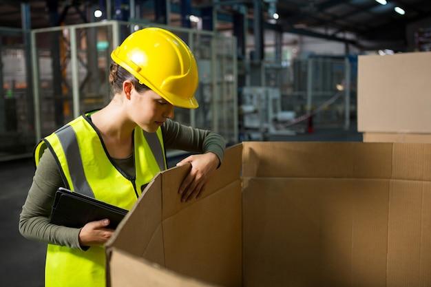 Arbeiterin, die produkte im lager prüft