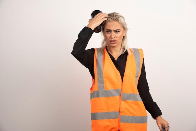 Arbeiterin, die sich auf weißem hintergrund verloren fühlt. hochwertiges foto