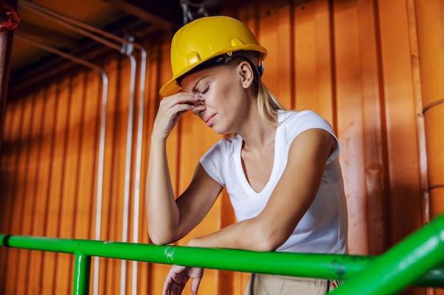 Arbeiterin, die sich in der fabrik auf ein geländer stützt und kopfschmerzen hat, weil sie überarbeitet ist
