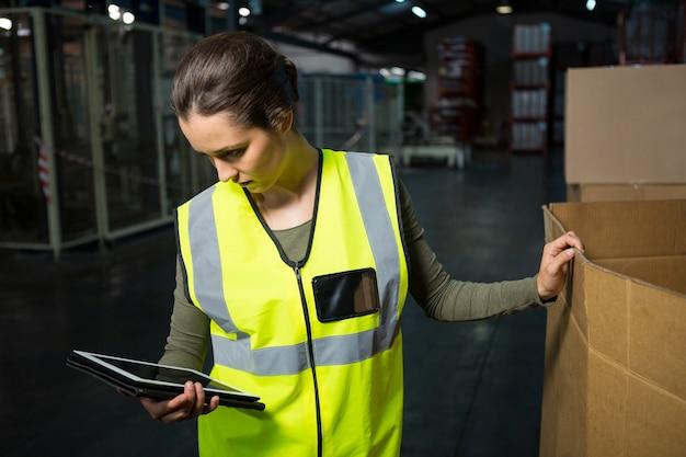 Arbeiterin, die tablett-pc im lager verwendet