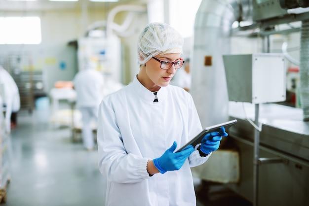 Arbeiterin, die tablette verwendet, um produkte zu steuern, während sie in der lebensmittelfabrik steht.