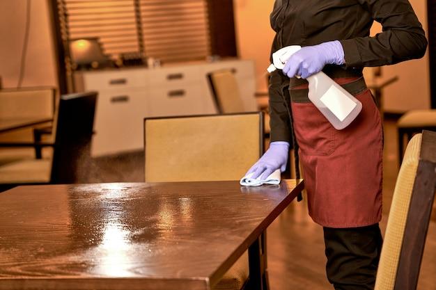 Arbeiterin im restaurant, die einen tisch mit einem tuch abreibt