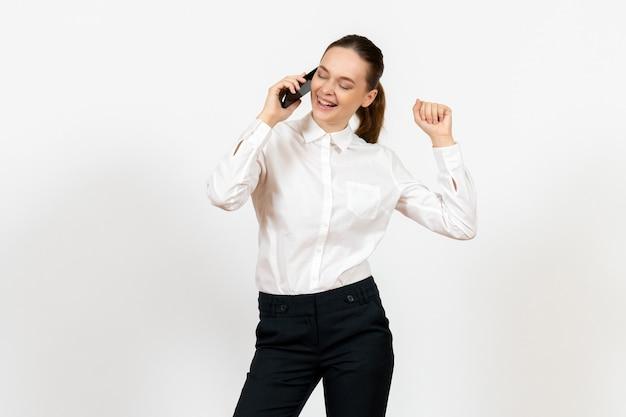 Arbeiterin in eleganter weißer bluse, die am telefon auf weiß spricht