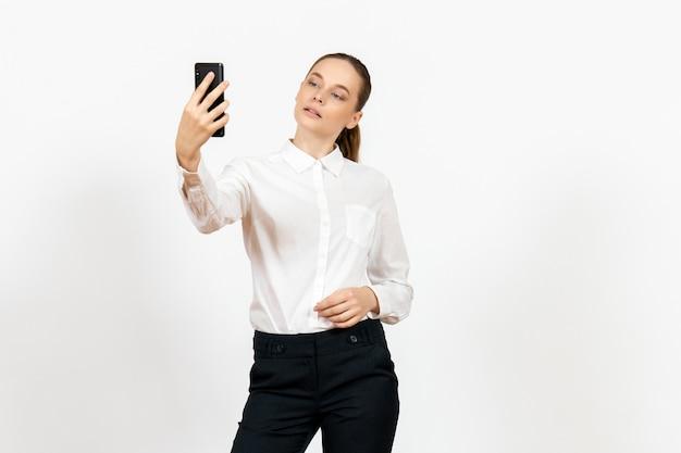 Arbeiterin in eleganter weißer bluse, die selfie auf weiß nimmt