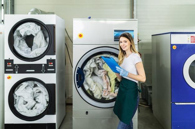 Arbeiterin lädt die wäsche in der reinigung in die waschmaschine.