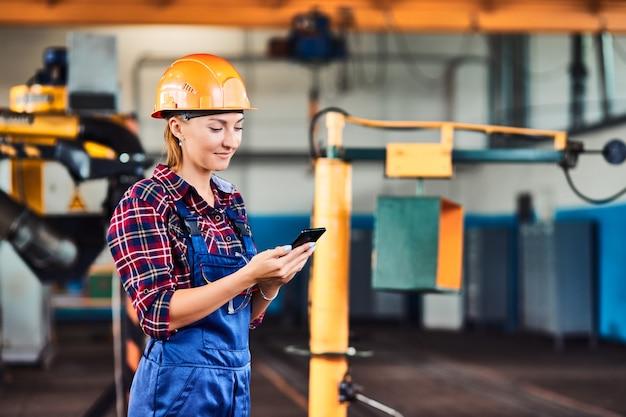 Arbeiterin mit den harten hüten an der industriefabrik, die im telefon schaut. konzept fauler arbeiter.