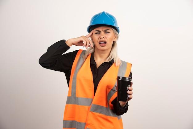 Arbeiterin mit tasse tee, der kopfschmerzen hat. hochwertiges foto
