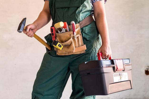 Arbeiterin mit werkzeugkasten und hammer