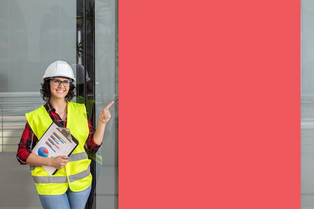 Arbeiterin mit weste und helm, die ein rotes plakat im hintergrund zeigt