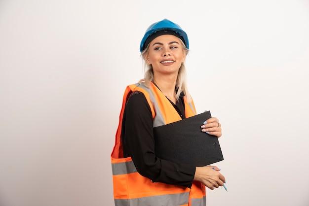 Arbeiterin mit zwischenablage, die auf weißem hintergrund aufwirft. hochwertiges foto