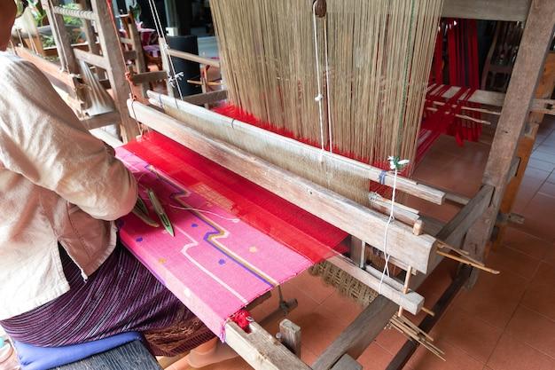 Arbeitermädchen, das den alten webstuhl spinnt