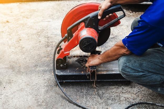 Arbeitermann, der stahl mit einem kreisförmigen stahlschneider schneidet.