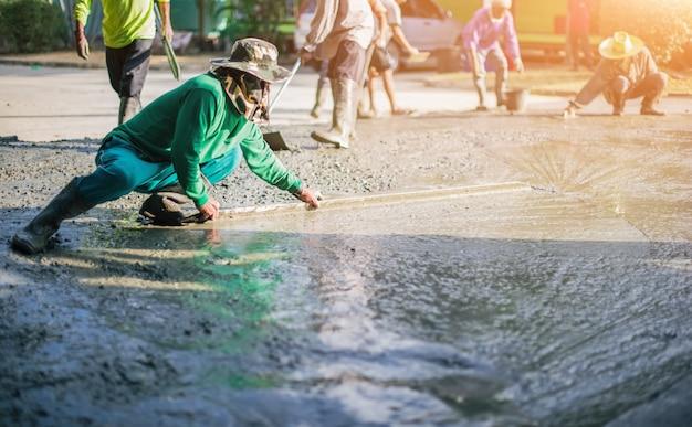Arbeiterpflaster an der baustelle, beton, der während der kommerziellen betonierböden gießt.