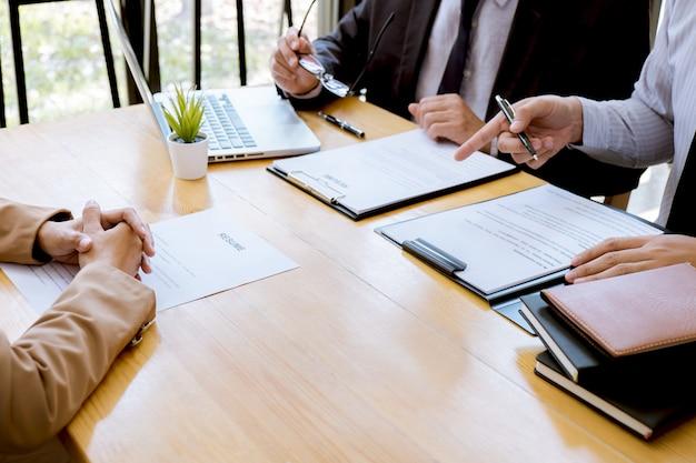 Arbeitgeber, der interviewt, um den jungen weiblichen arbeitssuchenden um die einstellung zu bitten, die im büro spricht