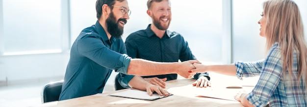 Arbeitgeber händeschütteln mit einer jungen frau während des interviews. konzept der zusammenarbeit