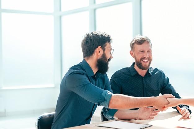 Arbeitgeber schüttelt einer jungen frau während des vorstellungsgesprächs die hand