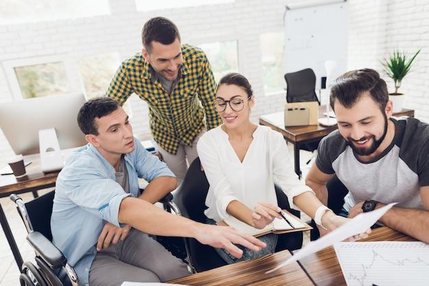 Arbeitnehmer und eine person im rollstuhl diskutieren arbeitsangelegenheiten