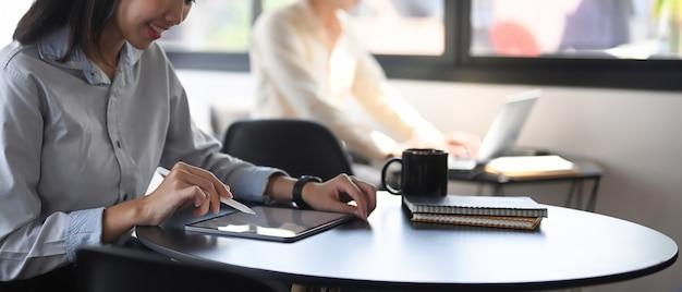 Arbeitnehmerin, die an einem digitalen tablet arbeitet, während sie mit ihrem kollegen im büro sitzt.